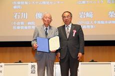 本学会特別顧問に推挙された岩﨑榮氏に末永理事長から特別顧問証が手渡された